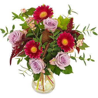 Bukett med blommor i ljust lila, cerice och gröna blad. Ett Euroflorist-arrangemang.