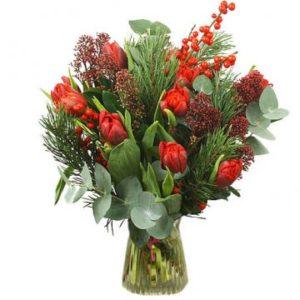 Julbukett med blommor i rött och gröna blad. Skicka julblommor med bud via Florister i Sverige!