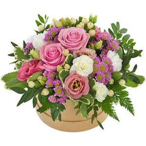 Söt,rund ask med blomsterdekoration i rosa, vitt och lila. Ett exklusivt blomsterarrangemang från Euroflorist.